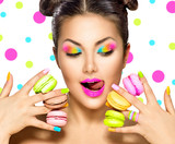 Fototapety Beauty fashion model girl with colourful makeup taking colorful macaroons