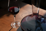 Closeup of the carafe and glass of red wine on the wooden table