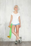 Fototapety Young woman with a skate in a white T-shirt and jeans shorts