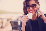Fototapety Young woman at cafe drinks coffee and talking on the mobile phone