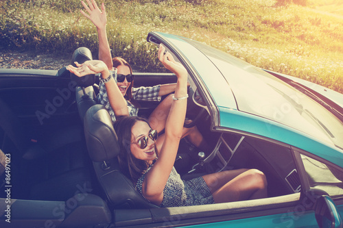 Poster Two attractive young women in a convertible car