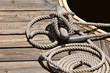 Deatil of boat tied to a woodn dock with nautical rope