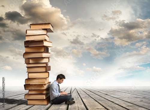 Poster, Tablou Column of books and young man with laptop