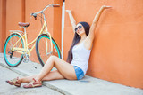 Sexy awesome asian woman sitting near the red wall background, there is a vintage city bicycle. She is freedom and raised her hands up, has happy vacation travel