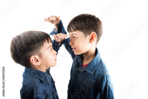 Little sibling boy brothers checking there tall each other Poster