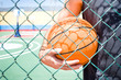 young man with the basketball behind a fence