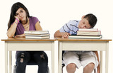 Studio shot on neutral background of two bored kids at their school desks.