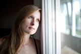 Mujer rubia mirando pensativa por la ventana