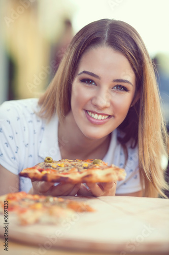 Portrait of cheerful young woman eating slice of pizza
