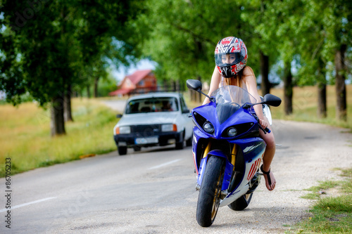 Foto op Canvas Scooter beautiful young woman with a motorcycle speed in nature