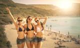 Fototapety Three girls posing at the beach