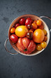 Assorted varieties of tomato in a colander
