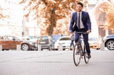 Handsome businessman riding his bicycle  - Fine Art prints