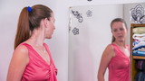 Woman trying new pink dress in front of mirror in slow motion