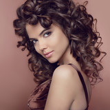 Fototapety Wavy hair. Attractive smiling girl with makeup. Curly hairstyle.