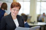 Frau im Büro liest ein Akte