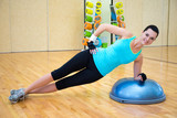 sporty woman doing exercises for abdominal muscles on bosu ball