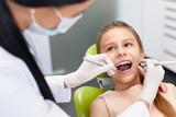 Teeth checkup at dentist's office. Dentist examining girls teeth