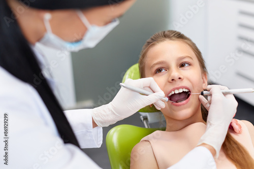 Teeth checkup at dentist's office. Dentist examining girls teeth Poster