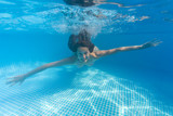 Underwater woman in swimming pool.