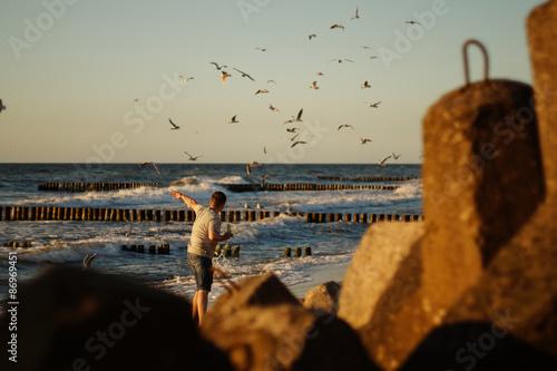 Mężczyzna karmi mewy na plaży.