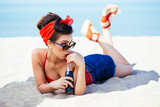 Pin-up at sea drink and watch over sunglasses