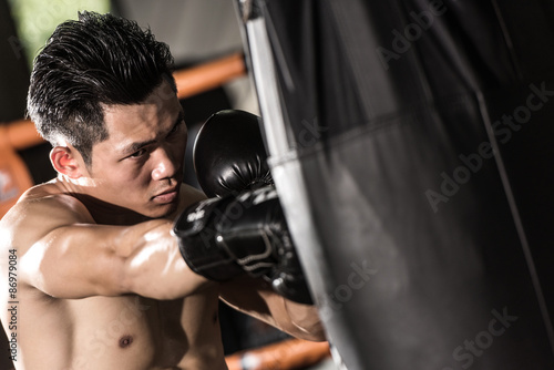 Poster young muscular fighter training on a punching bag in the gym