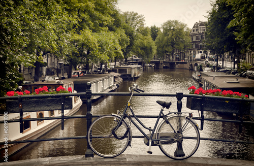 Poster Bicycle Parked on the Pedestrian Bridge Overlooking a Canal in Amsterdam