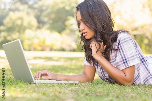 Keuken foto achterwand Boodschappen Pretty brunette lying in the grass and using laptop