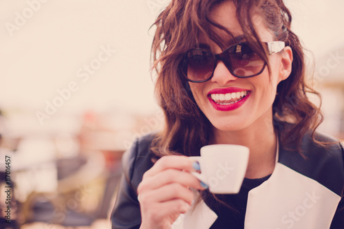 Young beautiful woman drinking coffee at cafe