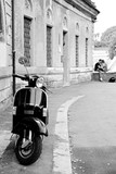Black and white photo of an iconic scooter with a young couple in the background.