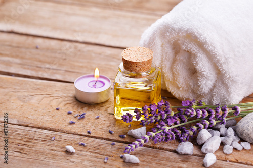Fototapeta Spa still life with lavender oil, white towel and perfumed candle on natural wood