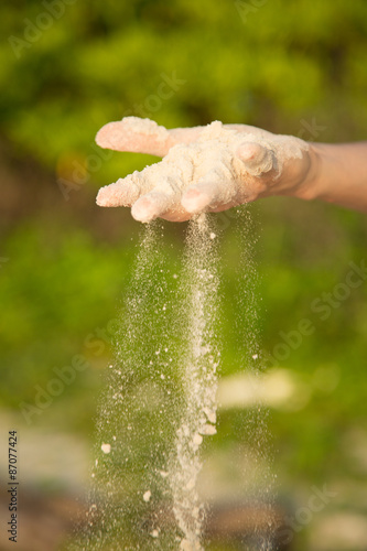 Poster Hand, with falling sand outdoor, green plant background