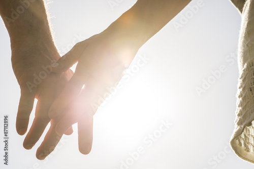 Romantic couple with clasped hands backlit by a bright evening s