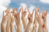 many hands showing victory sign, isolated on blue sky and clouds - 87160464