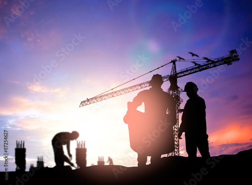 Silhouette engineer looking construction worker under tower cran