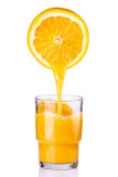 Fototapeta juice being poured into a glass of orange sliced on a white background