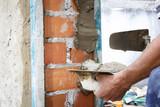 Obreros de la construcción trabajando en obra. Obras en el hogar. Reforma de fachada. Trabajador luciendo la fachada de una casa.