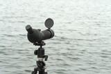 Birdwatching spotting scope monocular on a tripod near the water poster