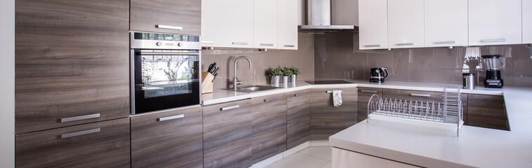 Wooden cupboards in cozy kitchen © Photographee.eu
