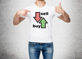 Close up of the man in denims and a white t-shirt pointing out to the chest with drawn arrows: buy and sell. The concept of the capital market and investor