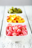 Fototapeta Colorful candies in bowl on white wooden background