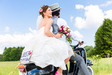 Fototapety Wedding couple on motor scooter just married