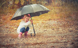 happy baby girl with an umbrella in the rain playing on nature