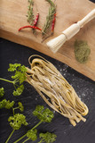 Raw fresh pasta tagliatelle decor with matcha greentea spice on background poster