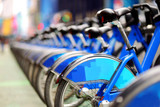 Fototapety Row of city bikes for rent at docking stations