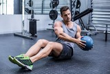 Muscular man doing russian twist exercises - 87568840