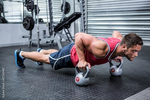Fototapeta Muscular man doing push-ups with kettlebells