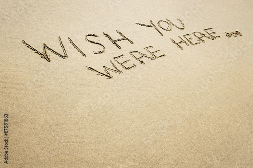 Poster Words wish you were here written in the sand on the beach.