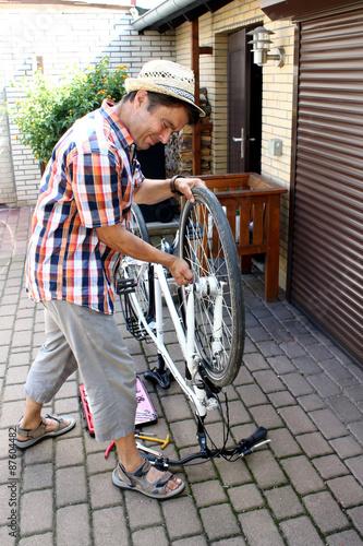 Deurstickers Fietsen Mann strengt sich bei Fahrradreparatur an. Verzieht Gesicht.